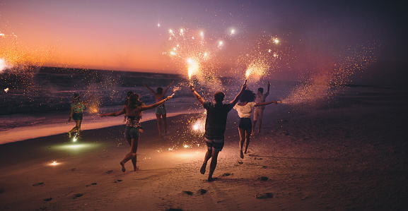 Friends running with fireworks on a beach after sunset