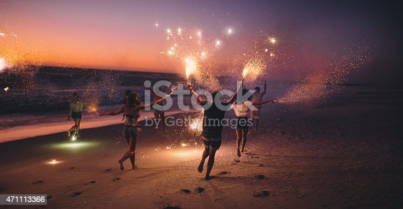 istock Friends running with fireworks on a beach after sunset 471113366