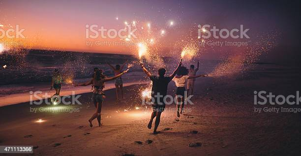 Friends Running With Fireworks On A Beach After Sunset Stock Photo - Download Image Now