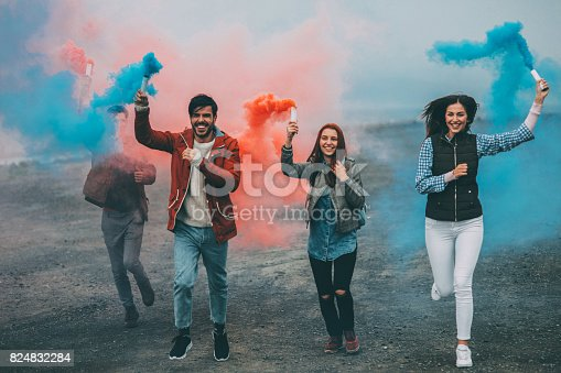 istock Friends running with smoke bombs in their hands 824832284
