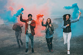 Friends running with smoke bombs in their hands
