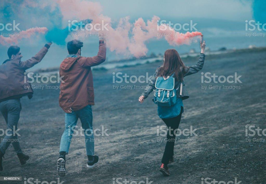 Amigos con bombas de humo en sus manos - foto de stock