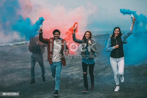 istock Friends running with smoke bombs in their hands 864925954