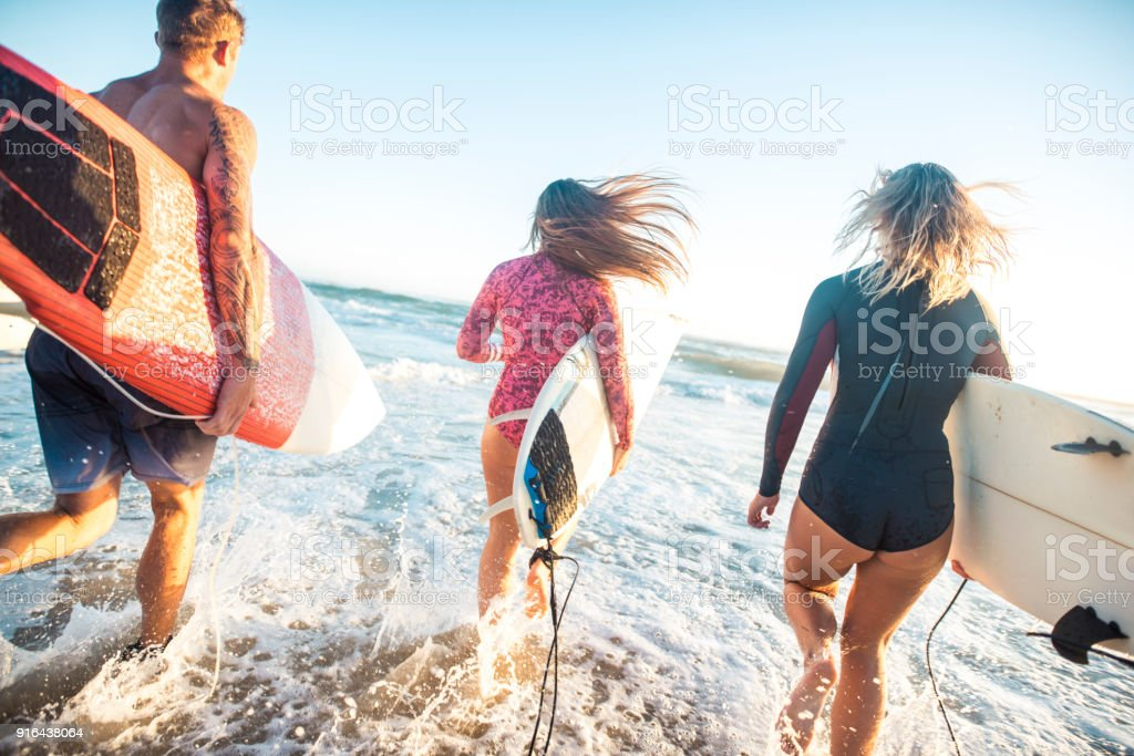 Friends running with surfboards into the ocean stock photo