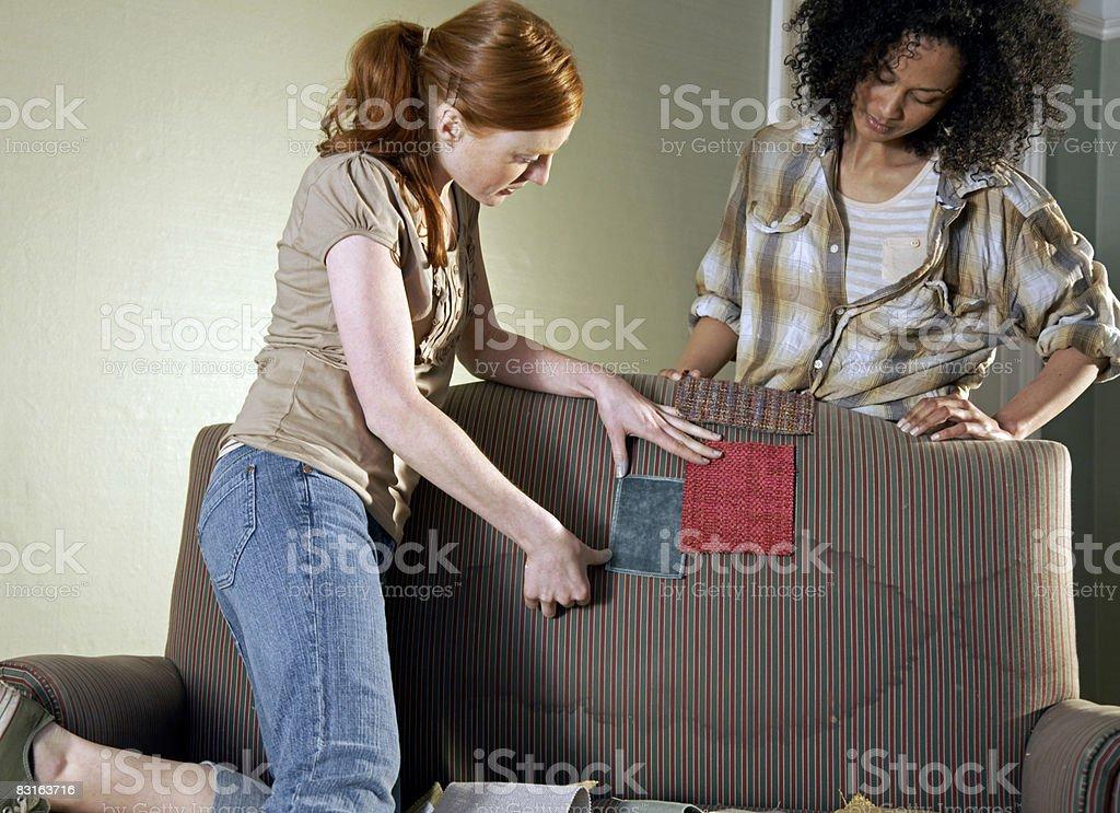 Amis dégustant de nouveaux échantillons contre un vieux canapé photo libre de droits
