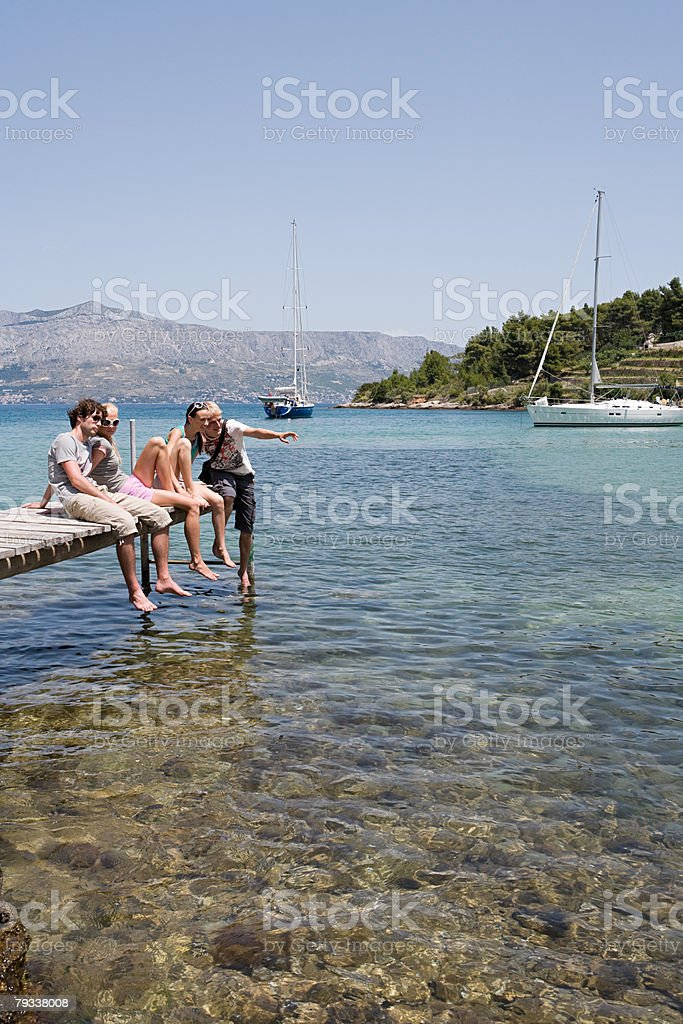 Friends sat on a jetty 免版稅 stock photo