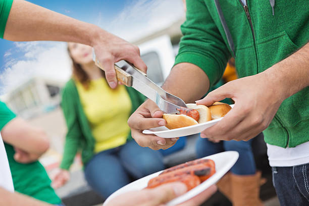 friends serving hot dogs and cooking out at tailgate party - serving size stock photos and pictures