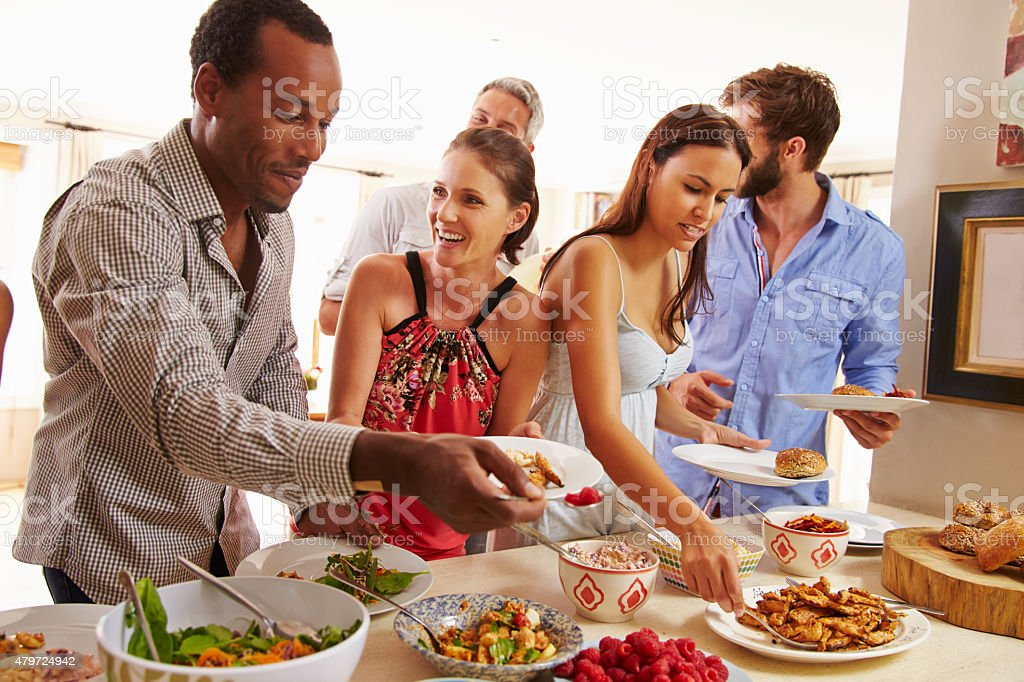Friends serving themselves food and talking at dinner party stock photo