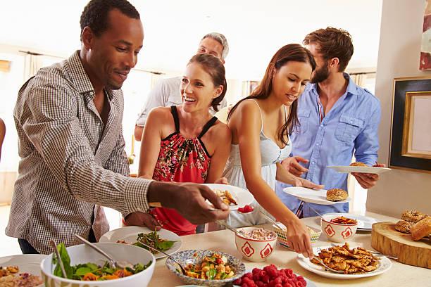 freunde mit sich selbst essen und gesprächen am dinner-party - esszimmer buffet stock-fotos und bilder