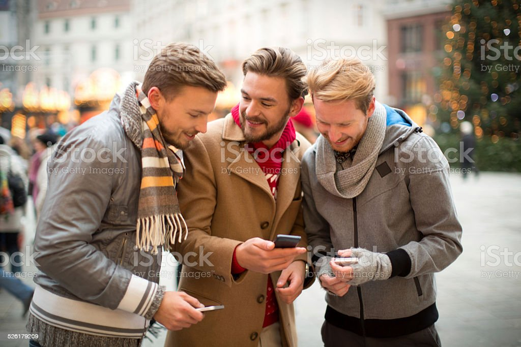 Friends sharing information on their smart phones. stock photo