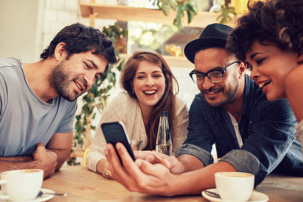 Friends sharing some photos on mobile phone stock photo