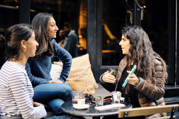Friends sharing stories with each other at a cafe stock photo