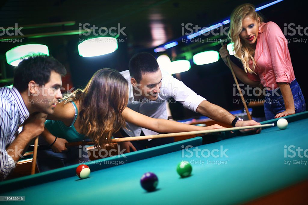 Group of mid 20\'s friends shooting pool on a weekend night out.One of...