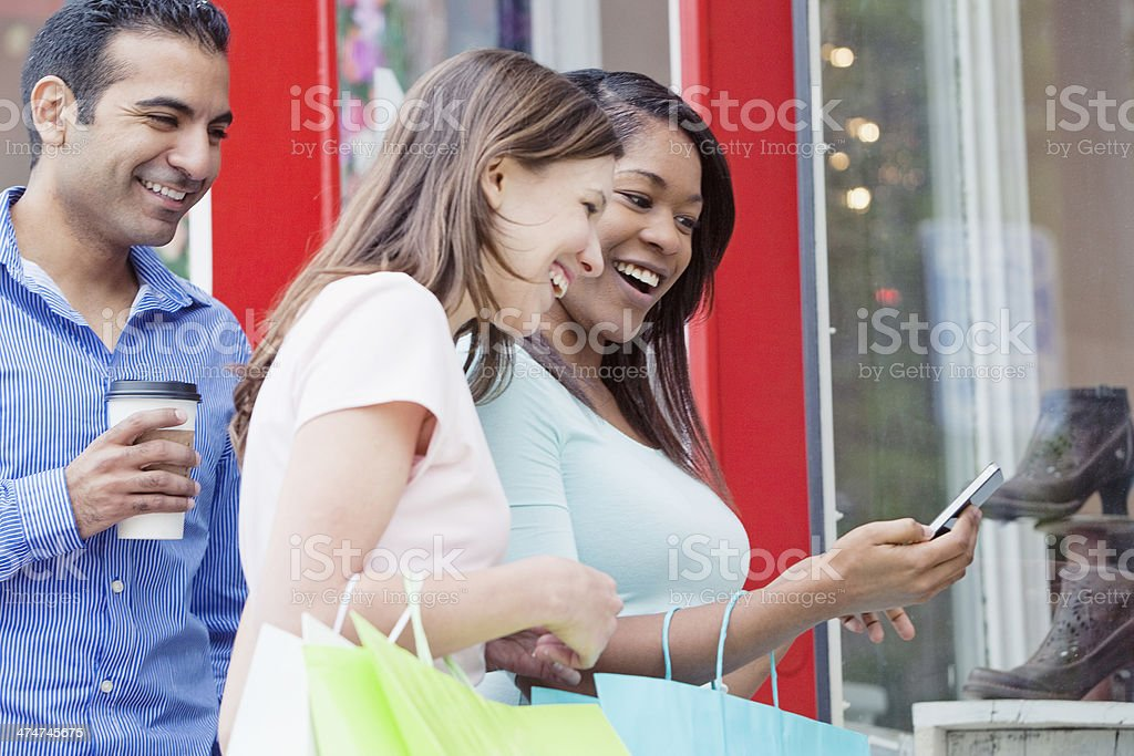 Friends Shopping and Comparing Prices on Smart Phone royalty-free stock photo
