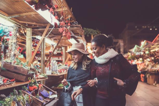 freunde, die weihnachtsgeschenke einkaufen - christkindlmarkt stock-fotos und bilder