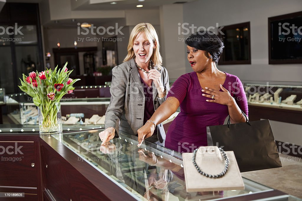 Friends shopping together in jewelry store stock photo
