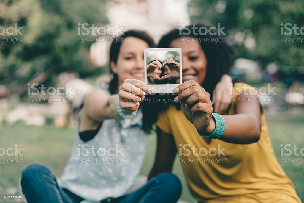 Amigos mostrando foto polaroid - foto de acervo