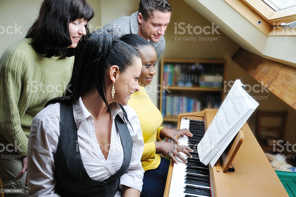 friends singing together round keyboard stock photo