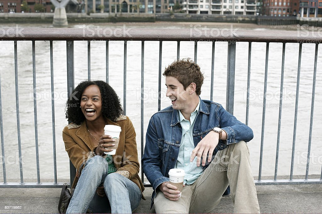 Friends sitting and laughing by river Thames royalty-free stock photo