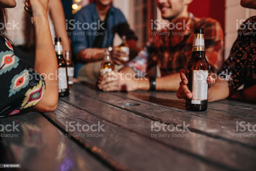 Friends sitting around a table having drinks – Foto