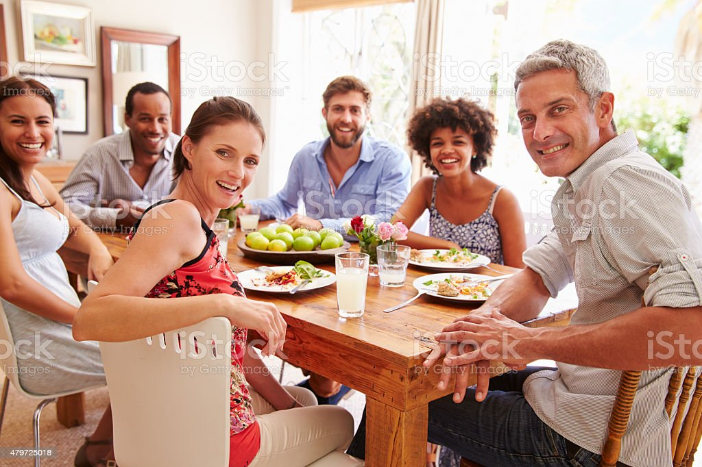 Friends sitting at a dining table, looking at camera stock photo