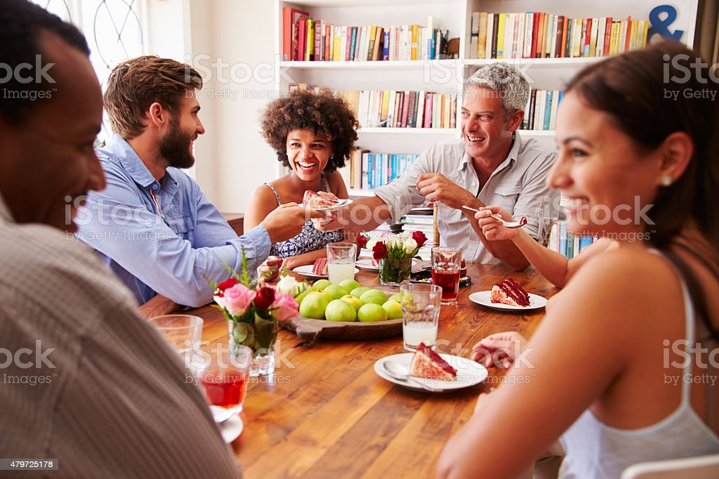 Friends sitting at a table talking during a dinner party stock photo