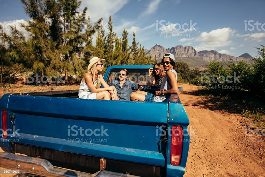 Friends sitting at the back of a pick up car stock photo