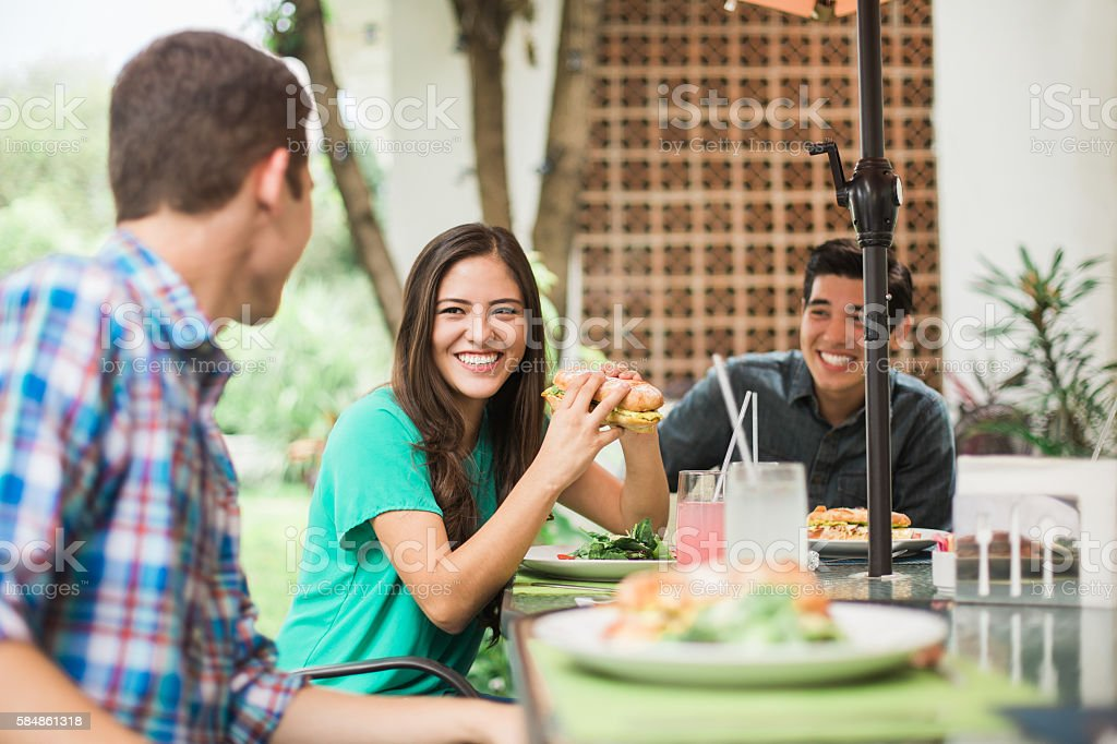Friends sitting at the table and eating stock photo
