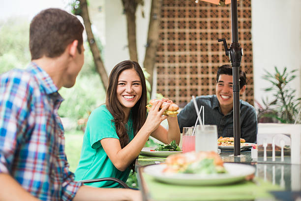 Friends sitting at the table and eating Three friends sitting at the table, eating a sandwich and smiling at each other in a horizontal waist up shot outdoors. submarine sandwich stock pictures, royalty-free photos & images