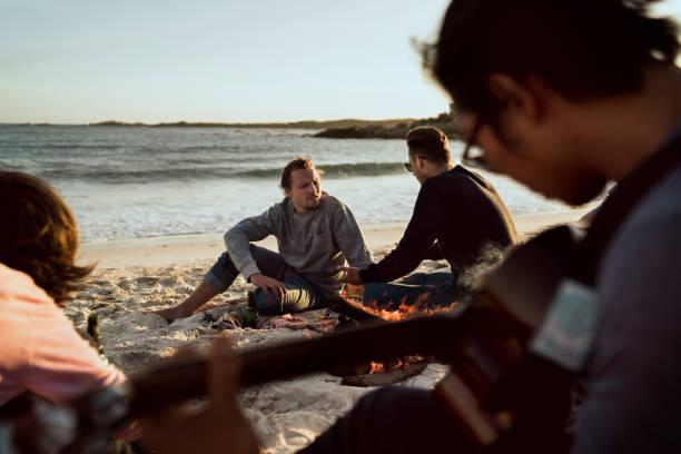 friends sitting by campfire at beach - falò spiaggia foto e immagini stock