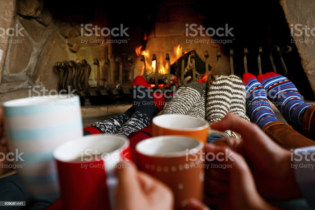 Friends sitting by the fireplace Four people warming their feet by the fireplace and drinking hot chocolate. Adult Stock Photo