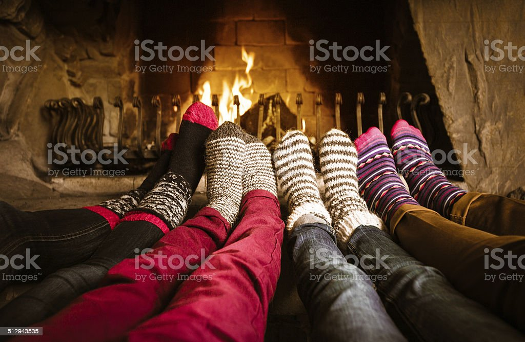 Friends sitting by the fireplace Four people warming their feet by the fireplace. Adult Stock Photo