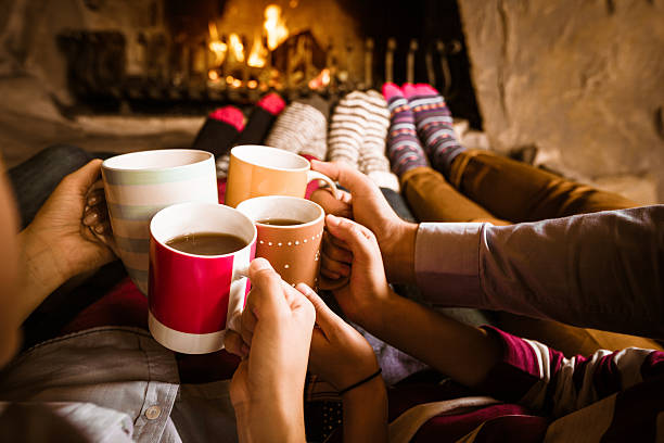 friends sitting by the fireplace - hot chocolate stock photos and pictures