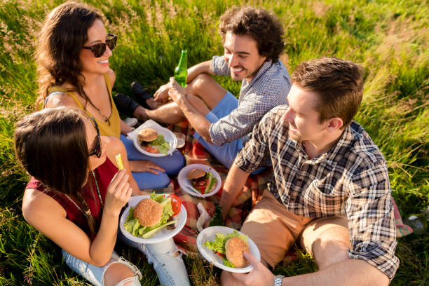 Friends sitting in grass and having burgers at barbecue party stock photo
