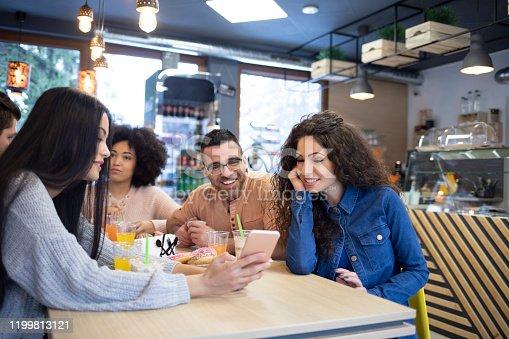 Friends sitting in restaurant and using phones, having fun.