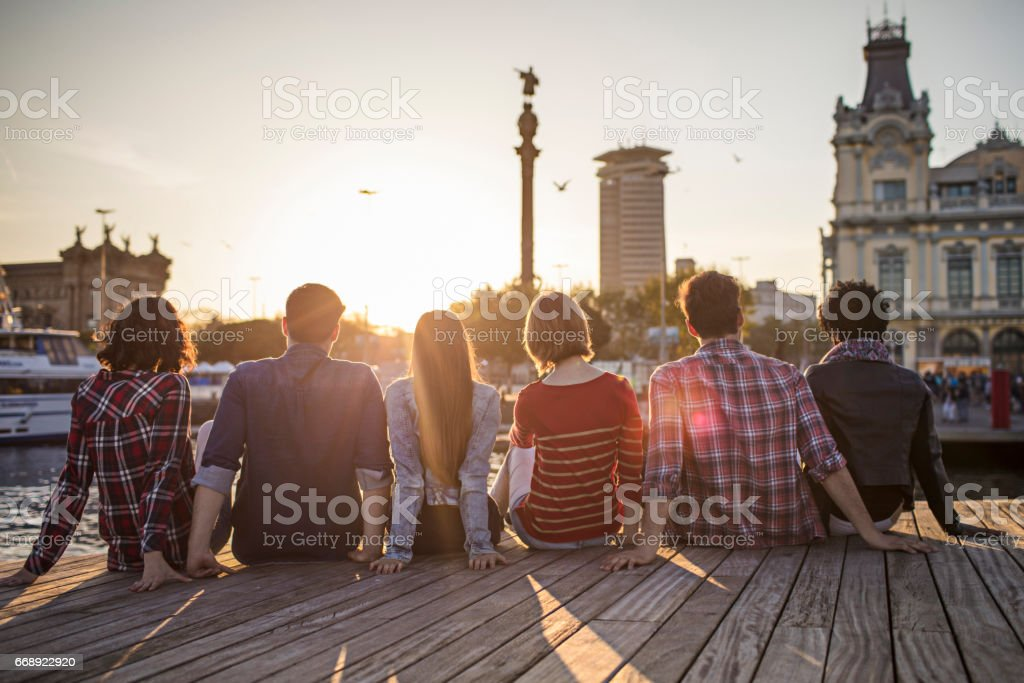 Friends sitting in row on boardwalk - foto de stock