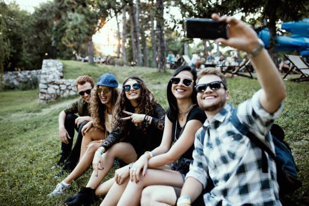 友人、草の中に座って笑いを持ち撮影 selfie ストックフォト