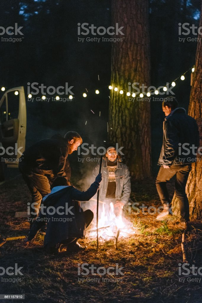 Young Caucasian men and woman sitting near campfire in the forest...