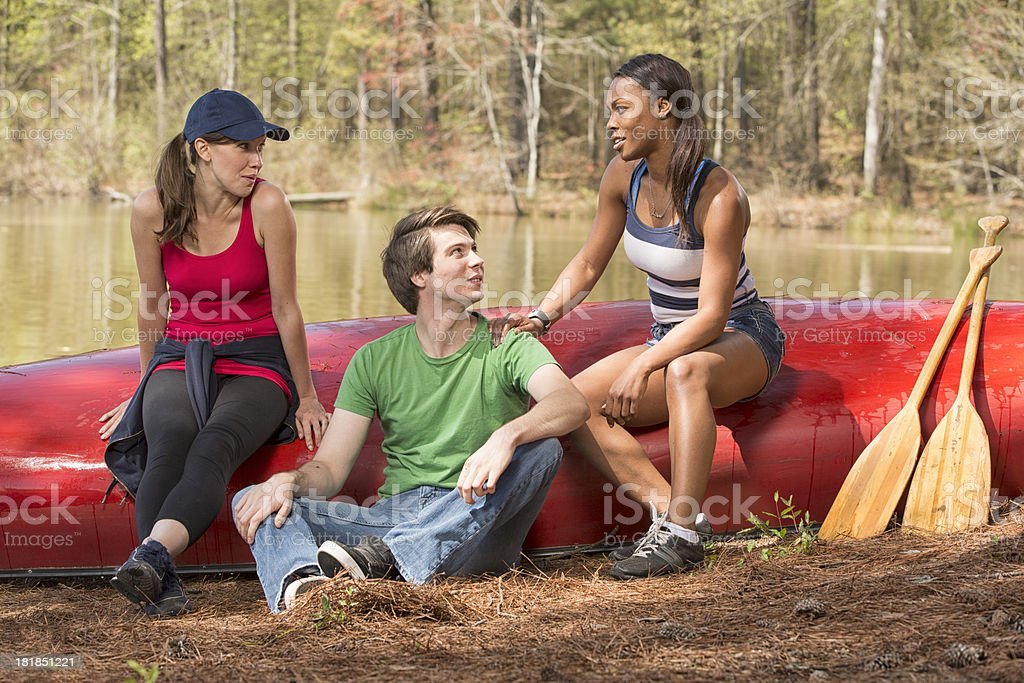 Friends sitting on a canoe, talking royalty-free stock photo