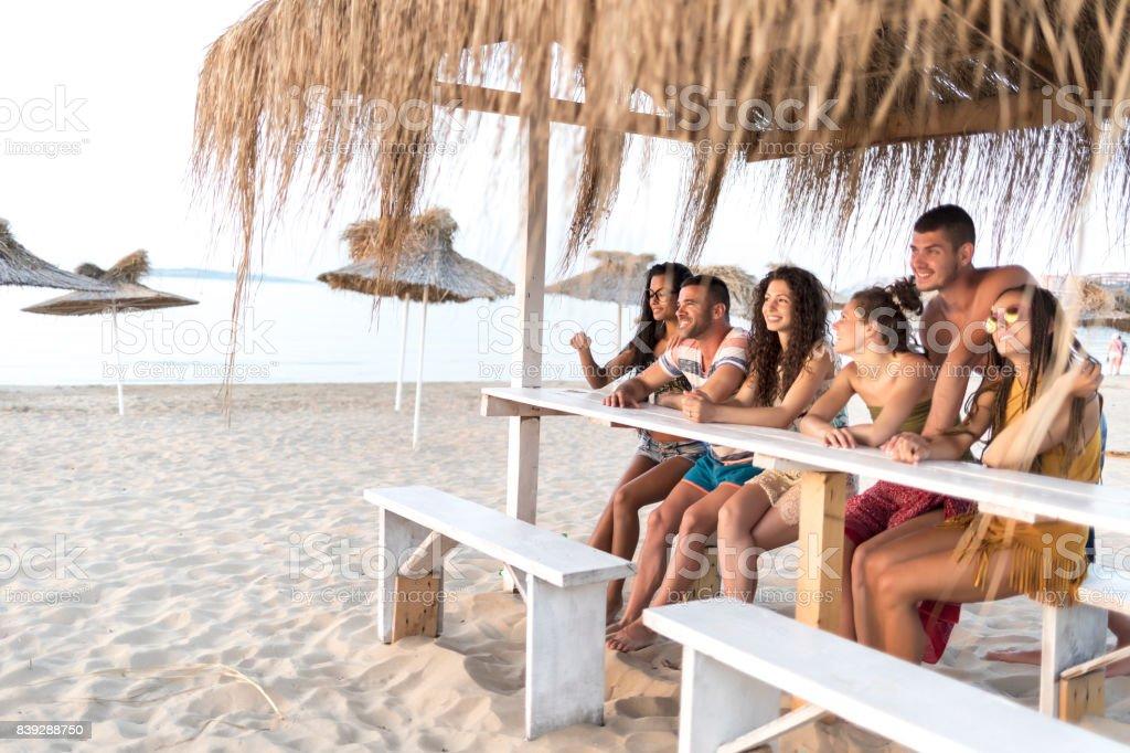 Friends sitting on beach bar stock photo
