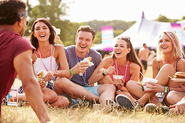 freunde sitzen auf gras und essen im music festival - mensch isst gras stock-fotos und bilder