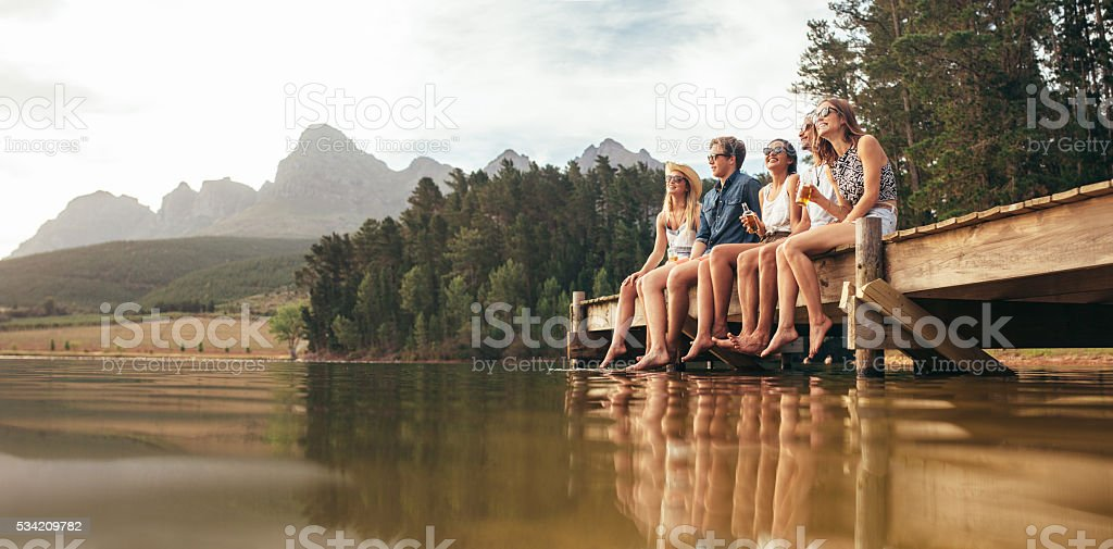 Friends sitting on pier at lake drinking beers stock photo