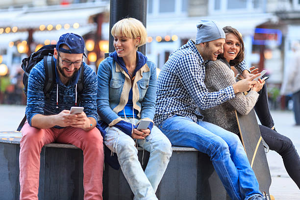 friends sitting on street and having fun - mobile game stock photos and pictures