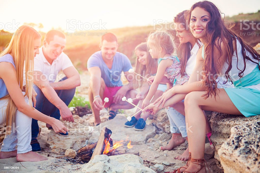 Friends sitting on the beach in circle with marshmallow stock photo