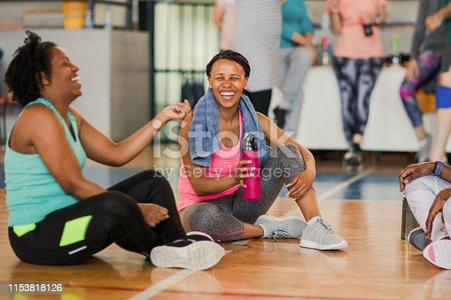 istock Friends sitting on the floor and talking after dance class while drinking water 1153818126