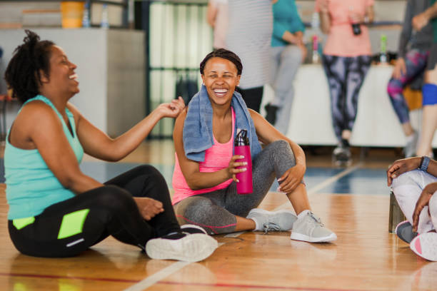 Friends sitting on the floor and talking after dance class while drinking water stock photo