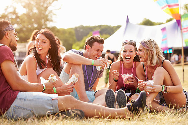 Friends sitting on the grass eating at a music festival stock photo