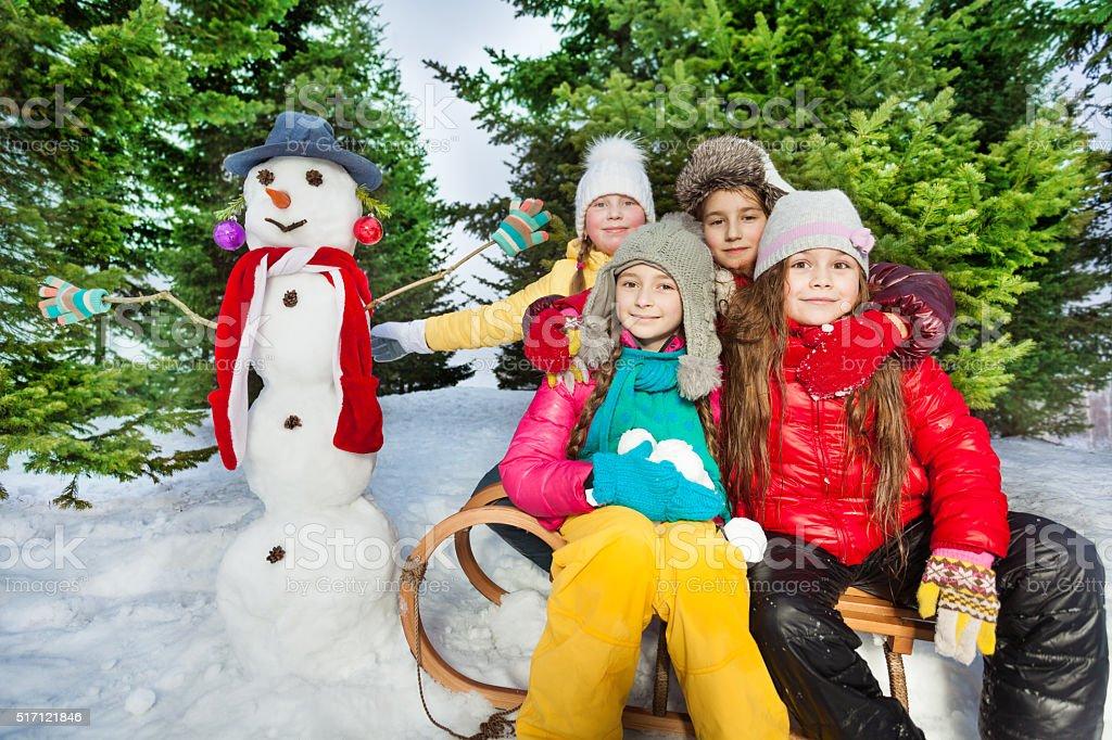 Friends sitting on the sledge near cute snowman stock photo