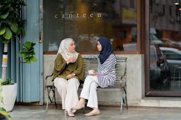 friends sitting outside drinking coffee and chatting - two students together asian foto e immagini stock