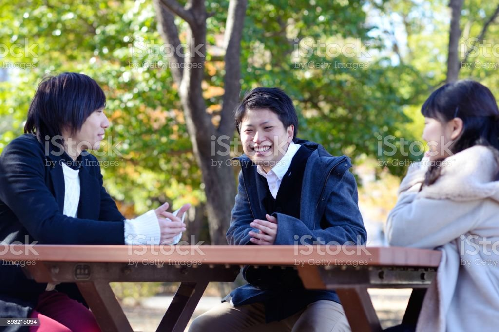 Friends sitting outside stock photo